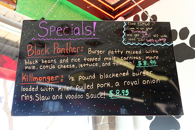 Candace H. Johnson-For Shaw Media A sign of hamburger specials honoring the superhero film, Black Panther, hangs from the wall in Bulldogs Grill on Main Street in Wauconda.The film references the fictional nation of Wakanda and the town of Wauconda and its businesses celebrate the recognition.