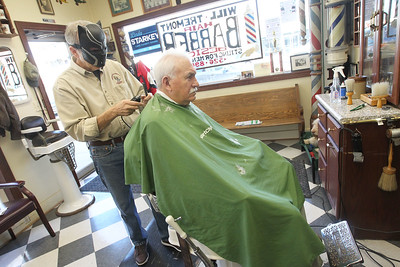 Candace H. Johnson-For Shaw Media Barber Will Tremont wears a Black Panther mask to honor the Black Panther movie as he gives a haircut to Nick Solideo, of Mundelein at Tremonte's Barbershop in downtown Wauconda.