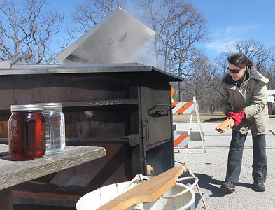 Candace H. Johnson-For Shaw Media Jen Berlinghof, of Chicago, environmental educator, puts firewood into the fire of an evaporator as it cooks sap from sugar maple trees used to make maple syrup at Ryerson Woods in Riverwoods.A jar of maple syrup and a jar of tree sap sits on a table to the left of the evaporator.(3/11/18)