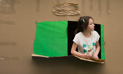 Whitney Rupp for Shaw Media Meghan Gau, 8, Crystal Lake, looks out a window during construction of her family's cardboard fort Saturday, March 17.