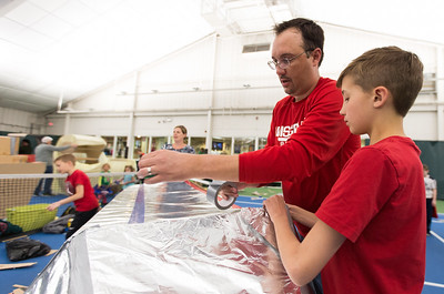 Whitney Rupp for Shaw Media Tony Santarelli, 10, helps dad Mike Santarelli, Crystal Lake, attach a roof to their rocket-themed fort Saturday, March 17.