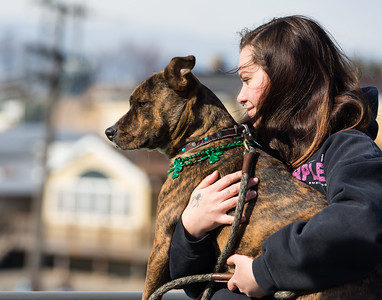 Whitney Rupp for Shaw Media Paige Delfino of McHenry and her dog, Buddha, watch the inaugural dyeing of the Fox River at Pearl Street Bridge Saturday, March 17.