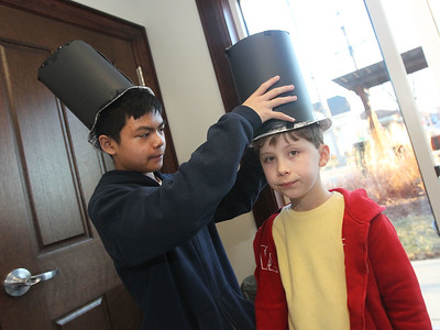 Candace H. Johnson-For Shaw Media Cale Amador, 13, helps James Foy, 8, both of Grayslake, put on the President Abraham Lincoln hat he made using paper plates and poster board at the Outside the Lines craft table during the Grayslake Arts Alliance Fine Art Show to highlight the Illinois Bicentennial Celebration at the Grayslake Heritage Center & Museum on Hawley Street in Grayslake.(3/17/18)
