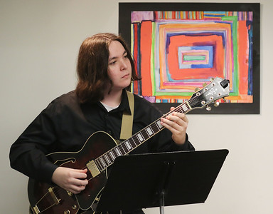 "Candace H. Johnson-For Shaw Media Thomas Power, 17, of Libertyville, a student with the Chapin Jazz Studio, plays the electric guitar beside a mixed media painting titled,"" Lynnie Leigh,"" by Heather June Toser, of Round Lake Beach during the Grayslake Arts Alliance Fine Art Show to honor the Illinois Bicentennial Celebration at the Grayslake Heritage Center & Museum on Hawley Street in Grayslake."