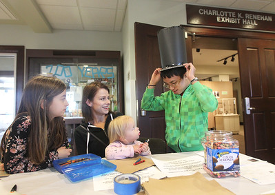 Candace H. Johnson-For Shaw Media Alyson Blaha, of Gurnee (second from left) and her daughters, Taylor, 9, and Evy, 2, look at Caden Amador's, 13, of Grayslake hat he made in honor of President Abraham Lincoln during the Grayslake Arts Alliance Fine Art Show to honor the Illinois Bicentennial Celebration at the Grayslake Heritage Center & Museum on Hawley Street in Grayslake. Caden was also helping the girls make a cave painting, the very first type of art to honor the Bicentennial of Illinois.(3/17/18)