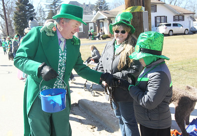 Candace H. Johnson-For Shaw Media Toni Watson, of Bristol, Wis., (center) watches Dan Venturi, Lake Villa Township supervisor, give some candy to her nephew, Russell Linder, 9, of Elk Grove Village during the Village of Lake Villa's Annual St. Patrick's Day Parade on Cedar Avenue in Lake Villa.(3/17/18)