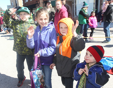 Candace H. Johnson-For Shaw Media Jacob Oess, 8, of Lindenhurst, Kailee Albeck, 7, of Round Lake and her brothers, Colton, 5, and Drake, 2, wave as they watch the Village of Lake Villa's Annual St. Patrick's Day Parade on Cedar Avenue in Lake Villa.(3/17/18)