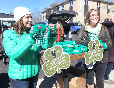 "Candace H. Johnson-For Shaw Media Sara McKinnon, of Long Grove, owner, and Conor McDowell, of Chicago, bar manager, hand out green gloves to promote the new Timothy O""Tooles' Pub opening soon in Lake Villa before the start of the Village of Lake Villa's Annual St. Patrick's Day Parade on Cedar Avenue in Lake Villa.(3/17/18)"