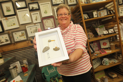 Candace H. Johnson-For Shaw Media Artist Laurel Fardoux, with The Found Pebble, shows off a stork picture she made with rocks and tumbled glass in her booth at Reclaimed Artisans Inc. in Libertyville.(3/17/18)