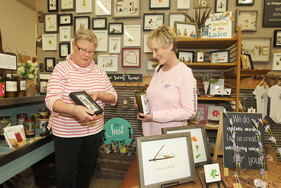 Candace H. Johnson-For Shaw Media Laurel Fardoux, with The Found Pebble, shows a hockey player picture she made using rocks and tumbled glass to Pam Wells, of Westmont on display and for sale at Reclaimed Artisans Inc. in Libertyville.(3/17/18)