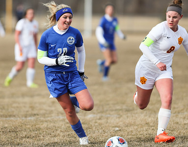 Whitney Rupp for Shaw Media Woodstock's Autumn Overly and Richmond-Burton's Sarah Kitterman race to the ball in a Kishwaukee River Conference game at R-B Tuesday, March 20.