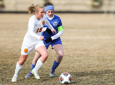 Whitney Rupp for Shaw Media Richmond-Burton's Darci Retherford and Woodstock's Grace Maidment work to keep the ball in play despite high winds during Tuesday's conference game at Richmond-Burton.