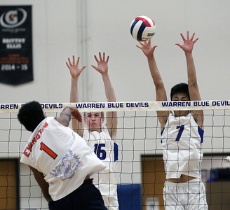 Candace H. Johnson-For Shaw Media Warren's Peyton Hines and Alex Jiang try to block a shot by Evanston's Darius Hunt in the first set at Warren Township High School in Gurnee. Warren won (25-11), (25-10).(3/19/18)