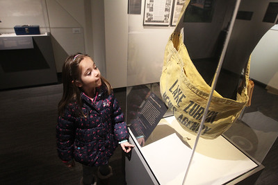 Candace H. Johnson-For Shaw Media Husna Saratore, 5, of Libertyville looks at a Newspaper Delivery Bag, used by Dick Price when he delivered newspapers in Lake Zurich when he was ten-years-old, during the Grand Opening of the Dunn Museum in the General Offices of the Lake County Forest Preserves on Winchester Road in Libertyville.(3/24/18)