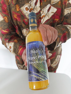 "Candace H. Johnson-For Shaw Media Archana ""Ana"" Dave, of Gurnee, and owner, holds a bottle of Healy's More! Mango premium mango wine she makes and bottles at the warehouse of Healy's Winery in Lake Villa.Healy's wines are sold at Woodmans in Wisconsin, Piggly Wiggly in Illinois and Wisconsin, and J's Liquor in Lake Villa.(3/26/18)"