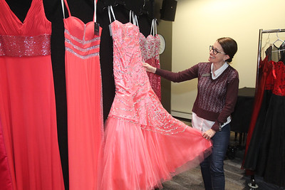 Candace H. Johnson-For Shaw Media Amanda Drummond, of Volo, circulation clerk, looks at the donated dresses hanging up for girls to try on in the Prom Dress Shoppe at the Wauconda Area Library. Girls could select one prom dress to take home for free from a selection of two hundred donated dresses.