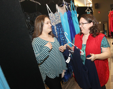 Candace H. Johnson-For Shaw Media Emma Robison, 14, of Island Lake gets some help from her mother, Magen, picking out a dress for her eighth grade dance at the Prom Dress Shoppe at the Wauconda Area Library.