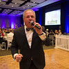 """Auctioneer Keith Jones crosses the dance floor while working for bids during the """"Spring In Paris Gala"""" fundraiser benefitting CASA Kane County at the Q Center in St. Charles on March 3."""