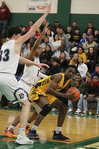Candace H. Johnson-For Shaw Media Carmel's Bryce Moore looks to make a pass against DePaul Prep's Brian Mathews and Lance Mosley in the third quarter during the Class 3A sectional semifinal game at Grayslake Central High School. DePaul Prep won 57-46.