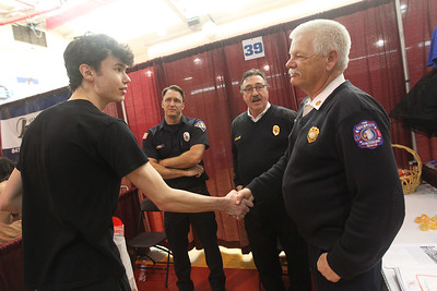 Candace H. Johnson-For Shaw Media Neil Knudsen, 17, of Round Lake shakes hands with Dave Becker, fire marshall, after talking to him along with Ted Damos, firefighter paramedic and Ron Hoehne, fire chief, all with the Fox Lake Fire Protection District during the Business & Craft Expo at Grant Community High School in Fox lake. The event was sponsored by the Fox Lake, Richmond and Spring Grove Area Chamber of Commerce. (3/2/19)