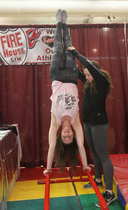 Candace H. Johnson-For Shaw Media Coaches Cieran Locke, of Ingleside has some help doing a handstand on parallel bars from Maggie Borst, of Crystal Lake while they promote Fire House Gym in Johnsburg during the Business & Craft Expo at Grant Community High School in Fox lake. The event was sponsored by the Fox Lake, Richmond and Spring Grove Area Chamber of Commerce. (3/2/19)