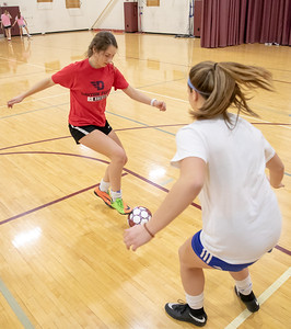 Prairie Ridge's Lucy Klimkowski (left) and Sam Gablenz (right) work on soccer drills Tuesday, March 12, 2019 in Crystal Lake. Weather has forced the team inside the gym for practice. KKoontz – For Shaw Media