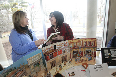 """Candace H. Johnson-For Shaw Media Cynthia Ripley Miller, a historical author, (on right) talks to her sister, Linda Hlavacek, both of Buffalo Grove, about two of her books in a three book series titled, """"On the Edge of Sunrise,"""" and """"The Quest for the Crown of Thorns,"""" during the Local Author Fair at the Wauconda Area Library. (3/9/19)"""