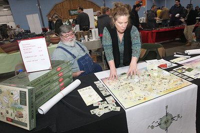 Candace H. Johnson-For Shaw Media Bob Hillemann, of South East, Missouri sits next to his sister, Susan Hogue, of Iberia, Missouri as she talks about the G.O.O.D. (Get Out of Dodge) KS Bunker game she created and was selling during the Survival & Green Living Expo at the Lake County Fairgrounds in Grayslake. (3/10/19)
