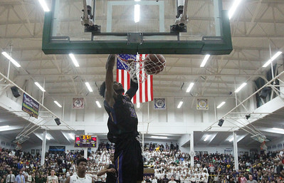Candace H. Johnson-For Shaw Media Waukegan's Bryant Brown scores a slam dunk against Stevenson's Cameron Bernard in the fourth quarter during the Class 4A sectional final at Waukegan High School. Stevenson won 56-41. (3/8/19)