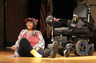 """Candace H. Johnson-For Shaw Media Army veteran Babette Peyton, of Chicago dances on the floor next to her wheelchair to the song, """"Here's to the Red, White and Blue,"""" during the Veterans Creative Arts Festival at the College of Lake County in Grayslake. (3/14/19)"""