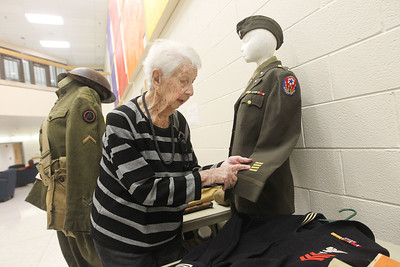 """Candace H. Johnson-For Shaw Media Dorothy Volkert, 95, of Antioch talks about the gold bars on a WWII nurses uniform on display as she relates it to her own experience as an Army nurse during WWII during the Veterans Creative Arts Festival at the College of Lake County in Grayslake. The exhibit titled,""""Uniforms from the Civil War Through Desert Storm,"""" were presented by George R. Gandara, of Chicago, an Army, Marine and National Guard veteran. (3/14/19)"""