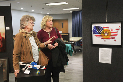 """Candace H. Johnson-For Shaw Media Barb Straub and Jill Callahan, both of Round Lake Beach look at an art piece made by Michael Beltchenko titled, """"We're an American Band,"""" during the Veterans Creative Arts Festival at the College of Lake County in Grayslake. (3/14/19)"""