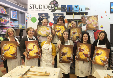 Candace H. Johnson-For Shaw Media Artists hold up their finished wine glasses paintings as they stand next to Amanda Munsen, of Ingleside, owner, in the middle, who taught them how to paint them during a Paint & Sip art class at Studio 25 Art Creations on Nippersink Blvd. in Fox Lake. (3/22/19)