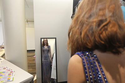 Candace H. Johnson-For Shaw Media Hallie Fedorowicz, 17, of Island Lake looks in the mirror as she tries on a dress for prom at the Prom Shoppe in the Wauconda Area Library. (3/23/19)