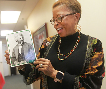 Candace H. Johnson-For Shaw Media Dr. Mary Roberson, social services supervisor and Navy veteran, talks about the photo of Frederick Douglass on display with other photos of prominent African Americans after the 4th Annual Chat N' Chew to honor African American Vets and Families during Black History Month at the Lake County Veterans and Family Services Foundation in Grayslake. (2/26/20)