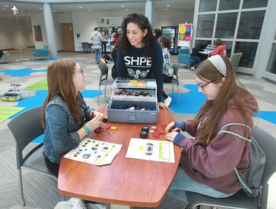 """Candace H. Johnson-For Shaw Media Paloma Alcala (center) helps Anastasia Habrych, 17, both of Round Lake Beach and Aspen Cronlund, 14, of McHenry build their own two-wheeled robot cars in the workshop called, """"Robots, Robots, Everywhere,"""" during the 10th Annual STEM for Girls at the College of Lake County in Grayslake. (2/29/20)"""