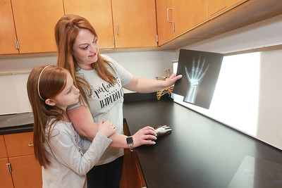 """Candace H. Johnson-For Shaw Media Heather Hallbom Sloma, of Gurnee shows her daughter, Vivien, 10,  an X-ray of a hand at the workshop called, """"Solving Mysteries: One Photo at a Time,"""" during the 10th Annual STEM for Girls at the College of Lake County in Grayslake.Heather is a senior student in the Medical Imaging program at the college. (2/29/20)"""
