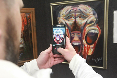 """Candace H. Johnson-For Shaw Media Ryan Deno, of Batavia, an Army veteran, uses his phone to photograph a painting titled, """"War Horrors: Faces from My Night Mares,"""" by Jerry Zabel on display during the annual Veterans Creative Arts Festival at the College of Lake County in Grayslake. The arts festival was presented by the Captain James A. Lovell Federal Health Care Center. (3/5/20)"""