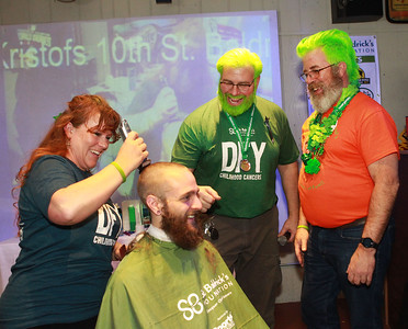 Candace H. Johnson-For Shaw Media Amanda Rogers, of McHenry, an independent hair stylist, works on shaving Jacob Kleinhardt's, of Waukegan head as they share a laugh with Tom Welninksi, of Antioch, and Mike Schmieg, of Volo, co-organizers, during the 10th Annual Kristof's Cares for Kids Rock the Bald St. Baldrick's Event in Round Lake Beach. (3/7/20)