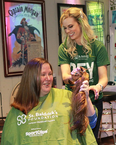 Candace H. Johnson-For Shaw Media Amanda Goeblirsch, of Fox Lake checks out how much of her hair was cut off by Jaide Janota, of Lake Villa, with Beauty by Jaide, during the 10th Annual Kristof's Cares for Kids Rock the Bald St. Baldrick's event in Round Lake Beach. (3/7/20)