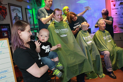 Candace H. Johnsoon-For Shaw Media Michelle Nowinski, of Spring Grove holds her son, Teddy, nine-months-old, as she watches her husband, Eric, son, Logan, 3, and father-in-law, Andrew, of Round Lake Beach, get their heads shaved on stage during the 10th Annual Kristof's Cares for Kids Rock the Bald St. Baldrick's event in Round Lake Beach. All three were getting their heads shaved in honor of Logan's little brother, Teddy, nine-months-old, who has neuroblastoma. (3/7/20)