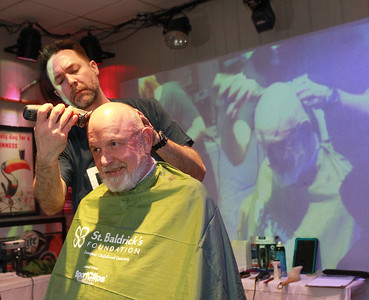 Candace H. Johnson-For Shaw Media Steve Kostelnik, of Vernon Hills gets his head shaved by Kevin Slimko, of Crystal Lake, a barber with Slim's Barber Shop, during the 10th Annual Kristof's Cares for Kids Rock the Bald St. Baldrick's event in Round Lake Beach. Kostelnik was at the event with his grandson, Griffin Fox, 13, of Grayslake, who also shaved his head.(3/7/20)