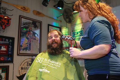 Candace H. Johnson-For Shaw Media Nick Garbett, of Antioch gets his head of hair and beard shaved off by Amanda Rogers, of McHenry, an independent hair stylist, during the 10th Annual Kristof's Cares for Kids Rock the Bald St. Baldrick's event in Round Lake Beach. (3/7/20)