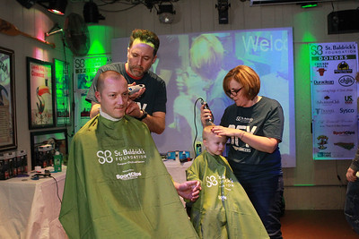 Candace H. Johnson-For Shaw Media Eric Nowinski, of Spring Grove holds hands with his son, Logan, 3, as get their heads shaved by Kevin Slimko, of Crystal Lake and Wendi Hutchings, of Wauconda during the 10th Annual Kristof's Cares for Kids Rock the Bald St. Baldrick's Event in Round Lake Beach. Both were getting their heads shaved in honor of Logan's little brother, Teddy, nine-months-old, who has neuroblastoma. (3/7/20)