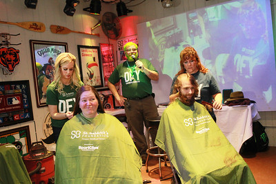 Candace H. Johnson-For Shaw Media Jaide Janota, of Lake Villa and Amanda Rogers, of McHenry, independent hair stylists, work with Amanda Goeblirsch, of Fox Lake and Jacob Kleinhardt, of Waukegan on cutting their hair during the 10th Annual Kristof's Cares for Kids Rock the Bald St. Baldrick's Event in Round Lake Beach. Tom Welninksi, of Antioch, co-organizer, stood behind them as he talked to the audience. (3/7/20)