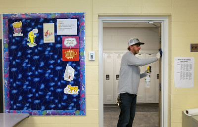 Candace H. Johnson-For Shaw Media Chad Rogers, of Round Lake Park, director of facility management, uses a disinfectant solution to wipe down a doorway of a 7th grade classroom at Gavin South Middle School in Ingleside. (3/16/20)