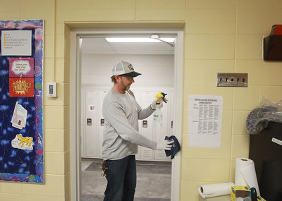 Candace H. Johnson-For Shaw Media Chad Rogers, of Round Lake Park, director of facility management, wipes down a doorway with a disinfectant solution in a 7th grade classroom at Gavin South Middle School in Ingleside. (3/16/20)