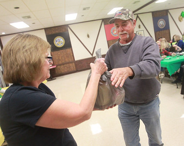 Candace H. Johnson-For Shaw Media  Diane Constanty, of Wauconda hands John Figiel, of Island Lake his prize during the Women's Auxiliary Meat Raffle at the Wauconda American Legion Post 911. The raffle was held to raise money for veterans and the community. (3/14/20)