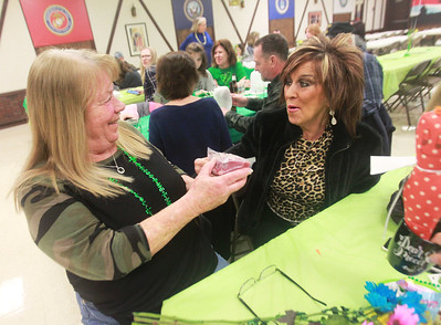 Candace H. Johnson-For Shaw Media  Kim Thoma, of Wauconda shows Dana Heff, of Lakemoor the package of meat she won during the Women's Auxiliary Meat Raffle at the Wauconda American Legion Post 911. The raffle was held to raise money for veterans and the community. (3/14/20)