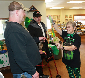 Candace H. Johnson-For Shaw Media  John Calhoun, of McHenry gets a medal from Sue Ryan, of Lake Villa, organizer, for the person who raised the most money to shave his head as Sam Lentine, of McHenry (in the middle) stands close by during the St. Baldrick's Foundation event at the Fox Lake Volunteer Fire Department in Ingleside.  (3/15/20)